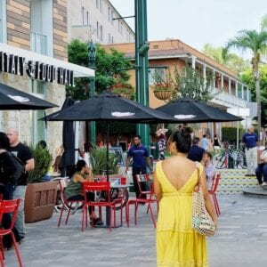 Photograph of a women in yellow walking outside of the Little Italy Food Hall
