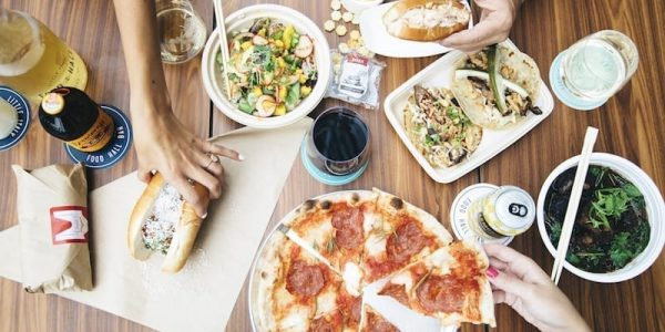 Bird's eye photograph of dishes from all the Little Italy Food Hall vendors which includes a pizza, tacos, lobster roll and meatball sub